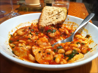 Seafood, Tomato and Cannellini Bean Stew on a plate served with crusty bread.