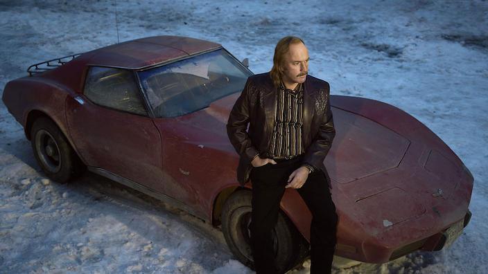 Fargo Season 3. Ewan McGregor sitting on a red car.