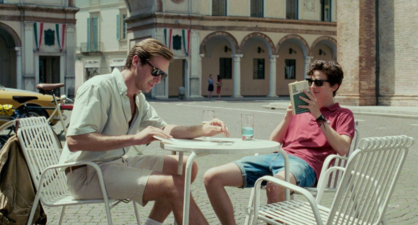 Call Me By Your Name. Armie Hammer as Oliver and Timothee Chalamet as Elio, sitting at a table in a piazza.