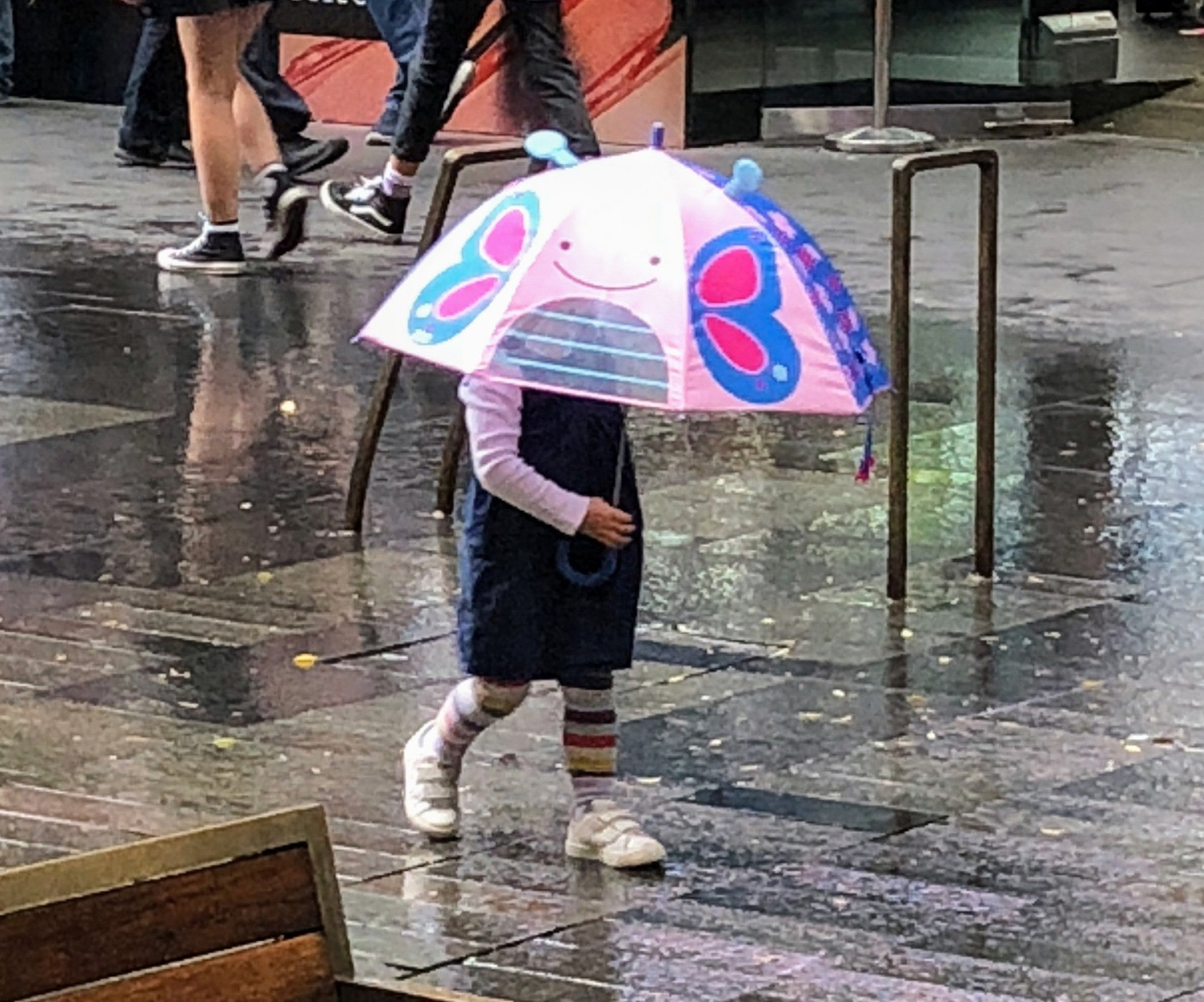 Girl walking in the rain with umbrella.